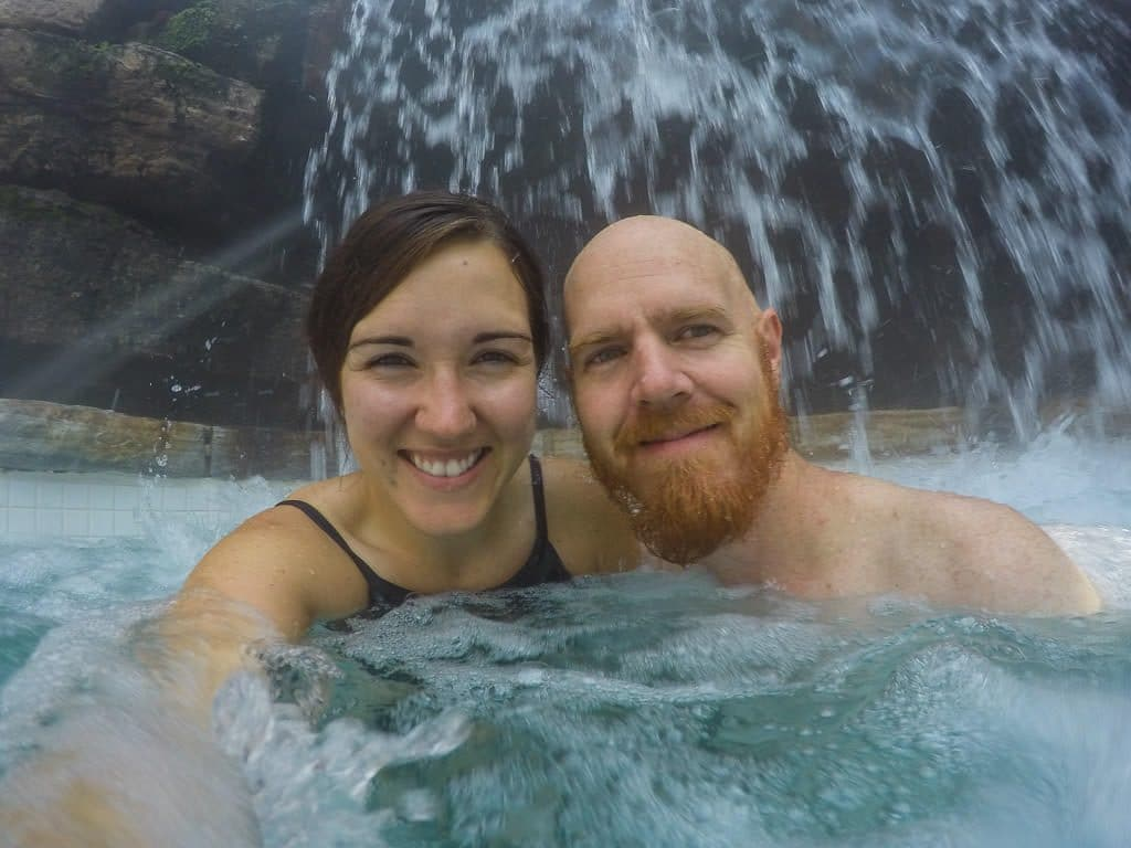 Brooke and Buddy taking a selfie under a waterfall at scandinave spa in mont-tremblant