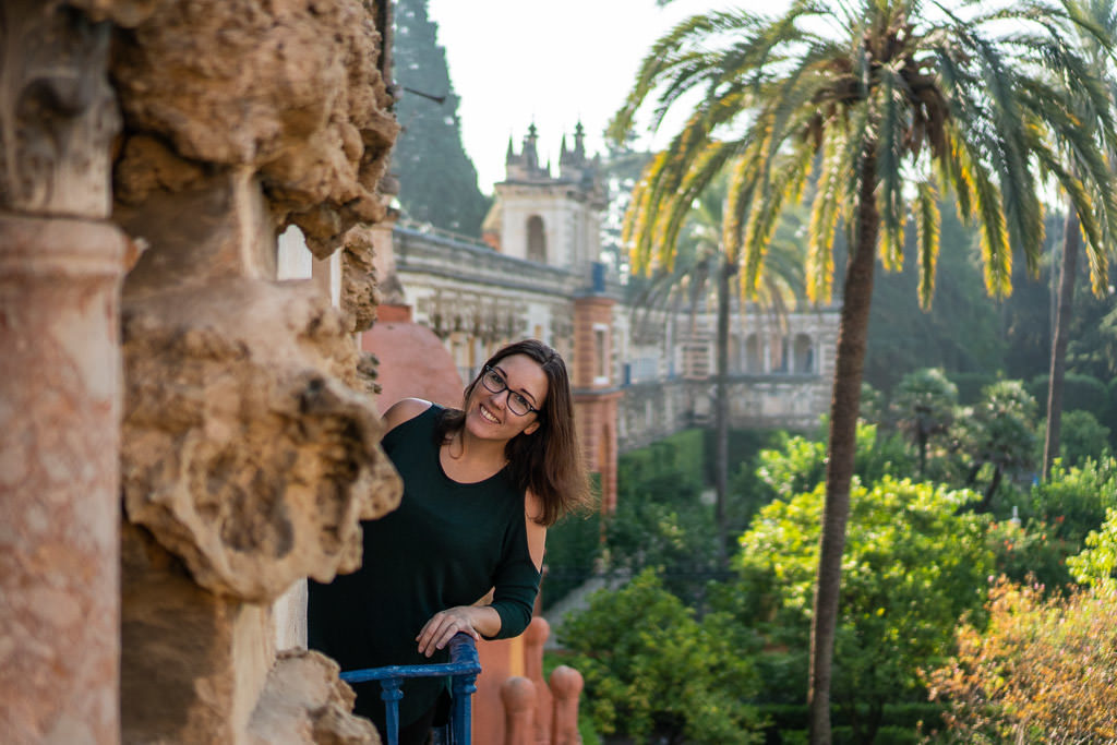 leaning over railing at ornate park at the real alcazar in seville spain
